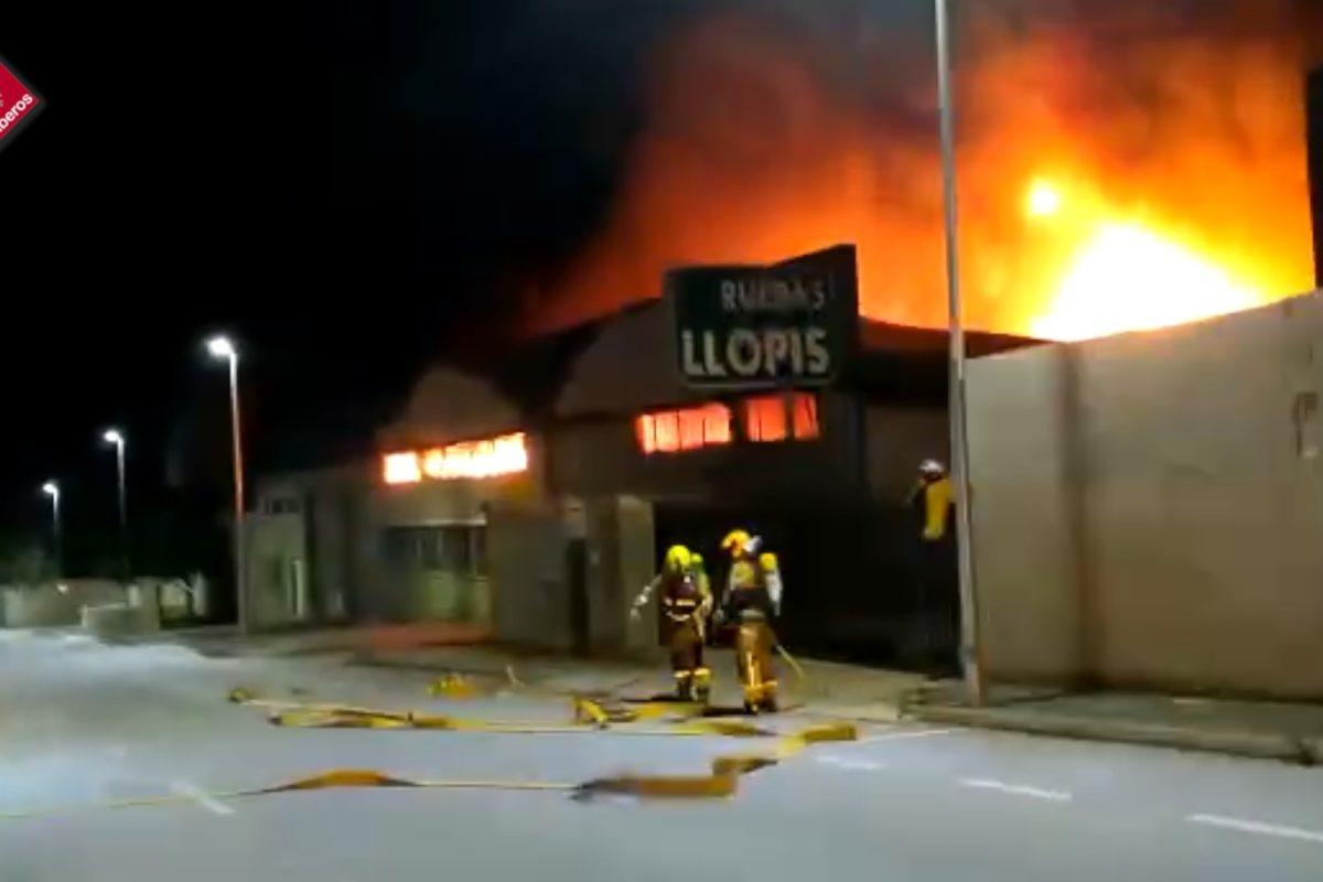 Els bombers treballen en l'extinció d'un incendi declarat en una nau de pneumàtics
